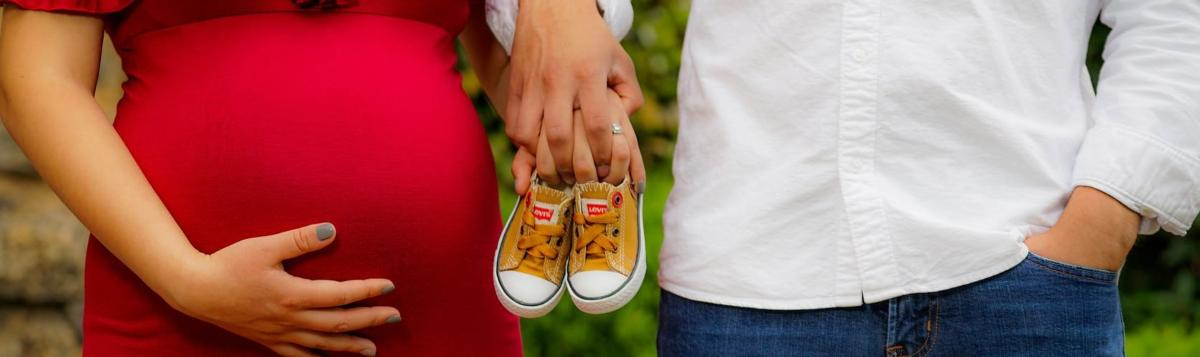 baby bump and baby shoes. man and woman holding hands